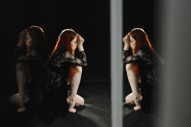 Uma ruiva atraente em lingerie preta senta-se no chão Foto gratuita