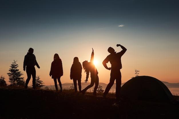 Uma silhueta de um grupo de pessoas se diverte no topo da montanha perto da tenda durante o pôr do sol. Foto gratuita