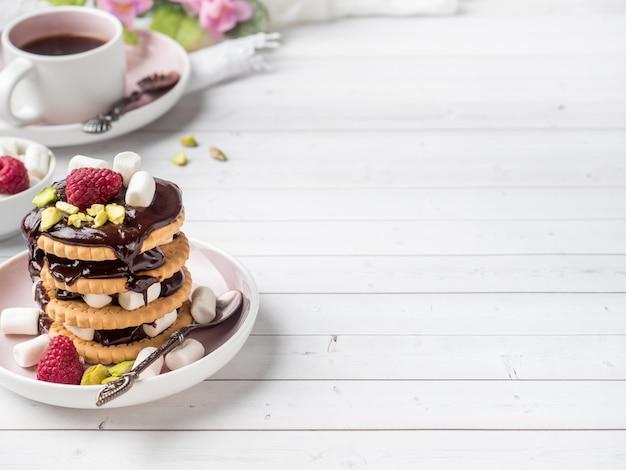 Uma sobremesa doce de um biscoito de chocolate framboesa e marshmallow xícara de café em uma mesa de luz Foto Premium