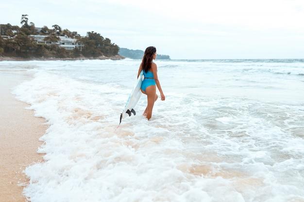Uma surfista linda com um corpo esbelto em biquíni e com prancha se divertindo na praia. Foto Premium