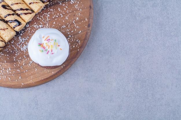 Uma tábua de madeira de palitos doces com bolinho cremoso com granulado colorido. Foto gratuita