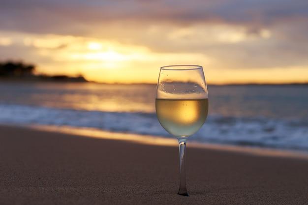 Uma taça de vinho branco na praia ao pôr do sol. Foto Premium
