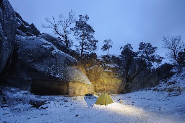 Uma tenda verde que está na neve ao lado do penhasco rochoso Foto Premium