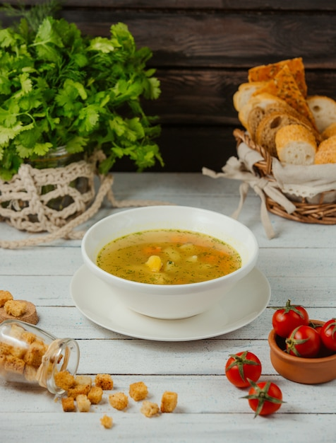 Uma tigela de sopa de galinha com batata, cenoura e endro, servida com fatias de pão Foto gratuita