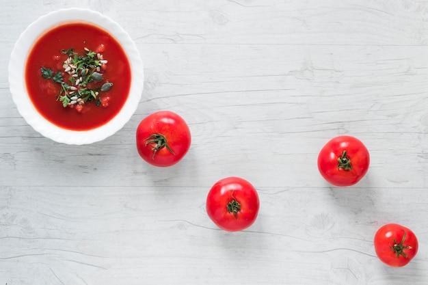 Uma tigela de sopa de tomate fresco em tigela de cerâmica branca, guarnecida com ervas e tomates maduros na mesa de madeira Foto gratuita