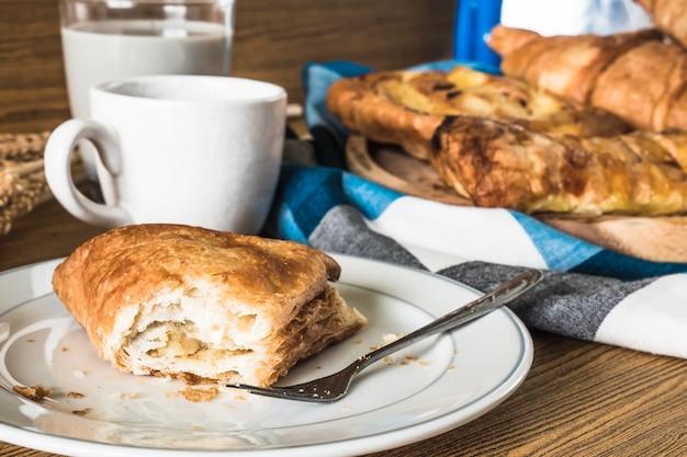 Uma torta no prato branco, variedade de doces com café e leite na mesa de madeira. Foto Premium