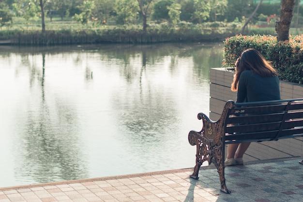 Uma triste, chateada e preocupada mulher sentada sozinha ao ar livre Foto Premium