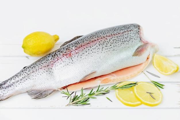 Uma truta decapitada crua em um fundo branco cortada em um lado com um limão e um alecrim deixa ao lado dele. peixe de água doce. Foto Premium