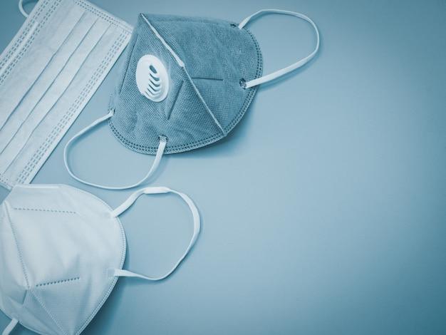 Uma variedade de máscaras é colocada em um plano de fundo cinza, com espaço para texto como uma ferramenta primária de prevenção durante a crise covid-19. conceito de autoproteção e saúde Foto Premium