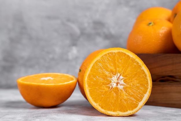 Uma velha caixa de madeira cheia de frutas inteiras e cortadas de laranja colocada em mármore Foto gratuita