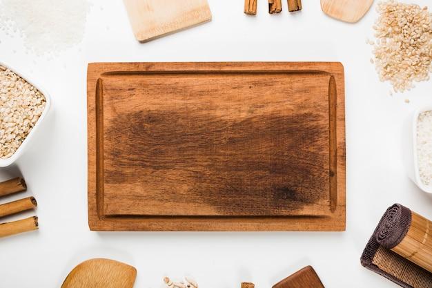 Uma visão aérea da bandeja de madeira vazia com espátula; arroz; paus de canela no fundo branco Foto gratuita