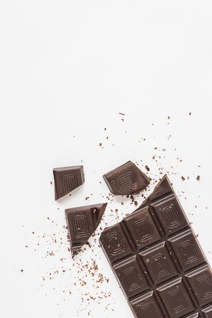 Uma visão aérea da barra de chocolate quebrada no fundo branco Foto gratuita