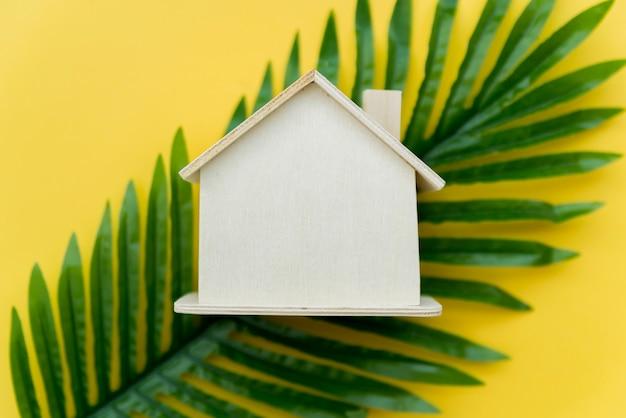 Uma visão aérea da casa de madeira sobre as folhas verdes contra um fundo amarelo Foto gratuita