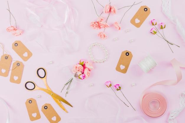 Uma visão aérea da fita; rosa artificial; pérolas; fita; tag e tesoura em fundo rosa Foto gratuita