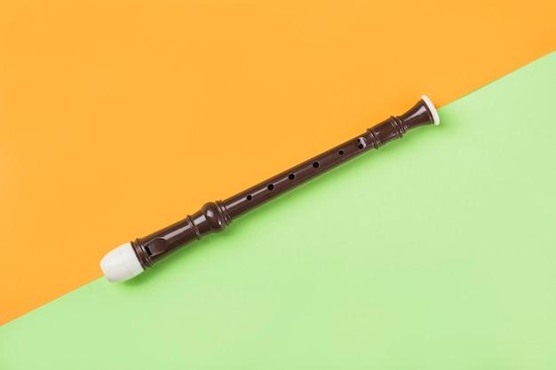 Uma visão aérea da flauta de bloco em fundo laranja e verde dual Foto gratuita