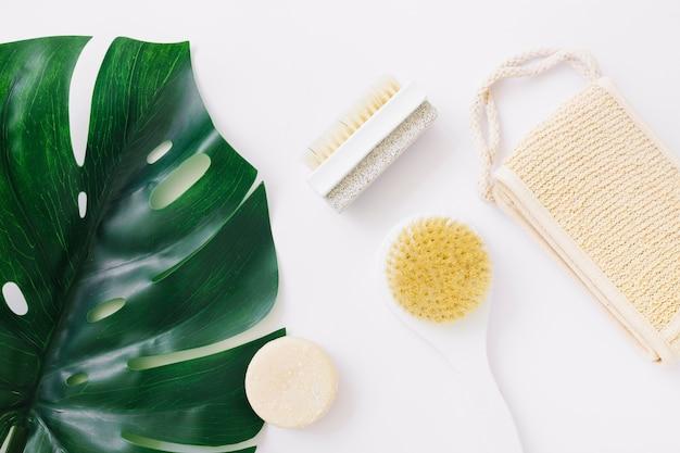 Uma visão aérea da folha de monstera com bucha; sabonete; escova e pedra-pomes escova de pedra sobre o pano de fundo branco Foto gratuita