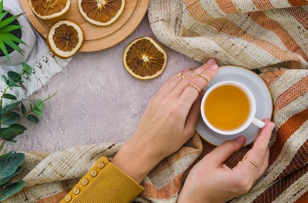 Uma visão aérea da mão de uma mulher segurando a xícara de chá de ervas e limão seco no pano de fundo texturizado Foto gratuita