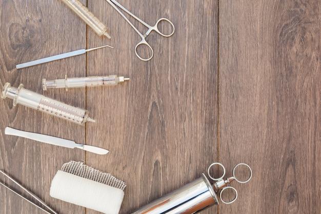 Uma visão aérea da seringa de aço inoxidável vintage; otoscópio e equipamentos médicos na mesa de madeira Foto gratuita