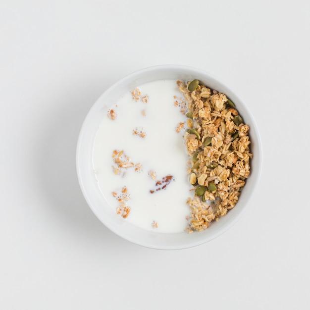 Uma visão aérea da tigela com aveia; leite e sementes de abóbora sobre fundo branco Foto gratuita
