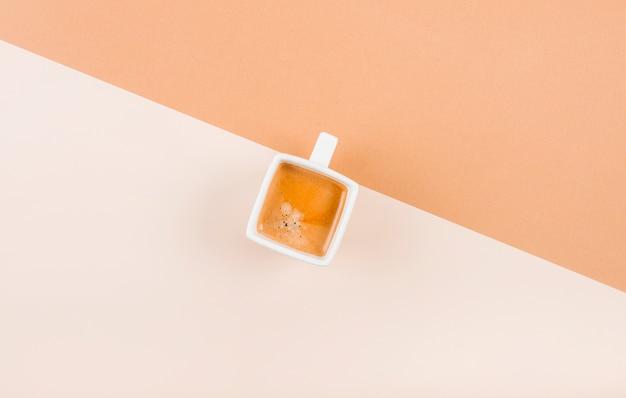 Uma visão aérea da xícara de café no fundo dual Foto gratuita
