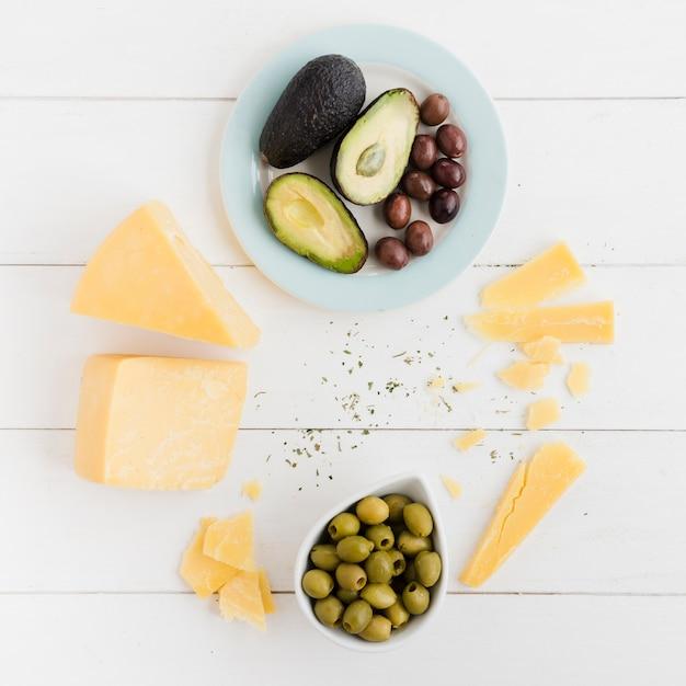 Uma visão aérea de abacate; azeitonas e queijo pedaço na mesa branca Foto gratuita