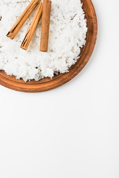 Uma visão aérea de arroz cozido com paus de canela na placa de madeira contra um fundo branco Foto gratuita
