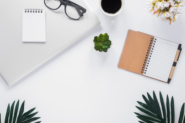 Uma visão aérea de artigos de papelaria do escritório com laptop; xícara de café; vaso de flor e folhas no pano de fundo branco Foto gratuita