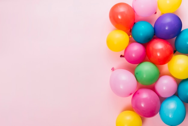 Uma visão aérea de balões coloridos sobre fundo rosa Foto gratuita