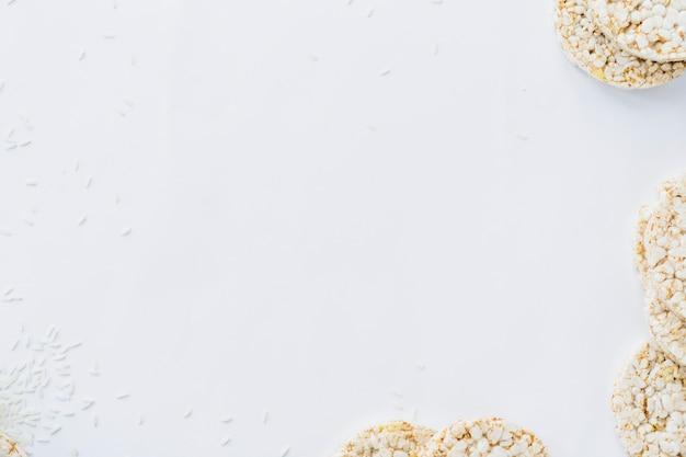 Uma visão aérea de bolos de arroz com grãos em papel branco Foto gratuita