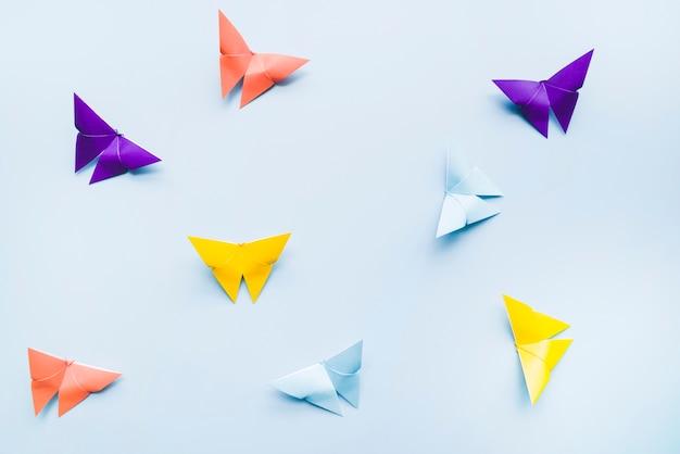 Uma visão aérea de borboletas de papel origami colorido sobre fundo azul Foto gratuita