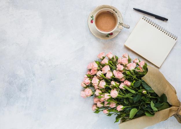 Uma visão aérea de buquê de flores cor de rosa; xícara de café; bloco de notas em espiral e caneta em pano de fundo concreto Foto gratuita