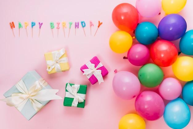 Uma visão aérea de caixas de presente coloridas; balões e velas de feliz aniversário no pano de fundo rosa Foto gratuita