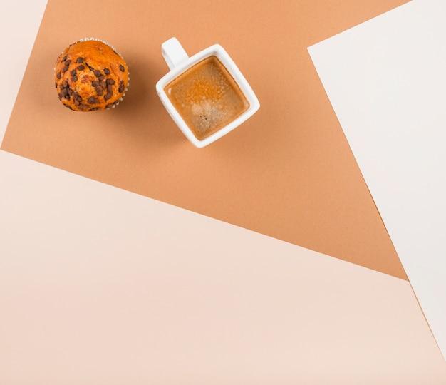 Uma visão aérea de cup cakes e xícara de café no pano de fundo duplo bege Foto gratuita