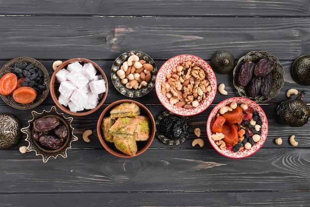 Uma visão aérea de doces árabes e frutas secas para o ramadã na mesa de madeira preta Foto gratuita