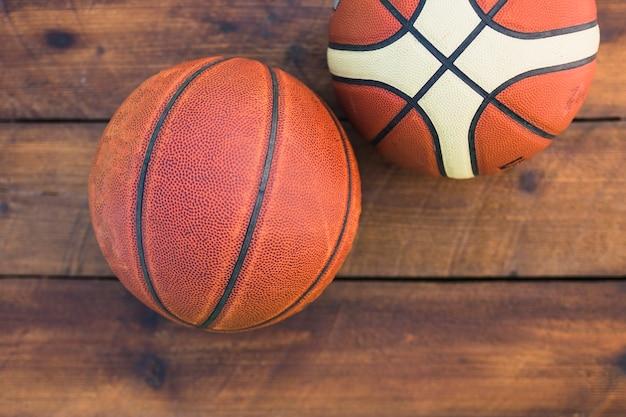 Uma visão aérea de dois basquete no plano de fundo texturizado de madeira Foto gratuita