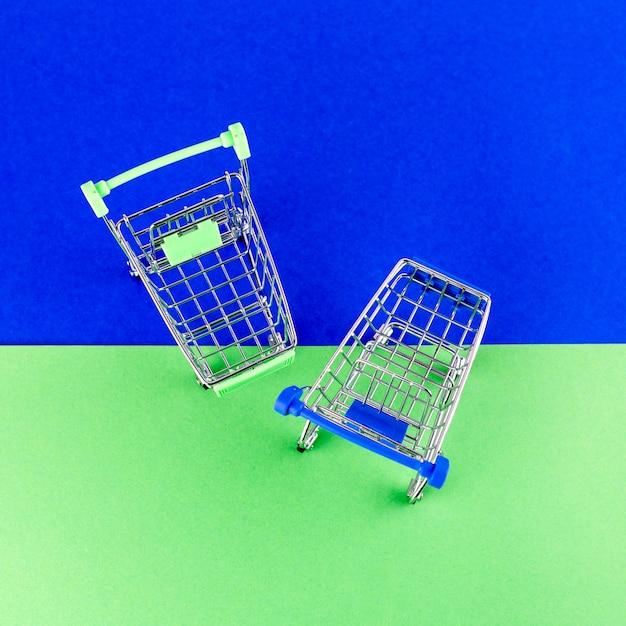 Uma visão aérea de dois carrinhos de compras em fundo azul e verde Foto gratuita