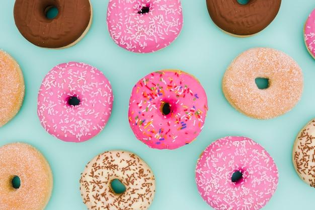 Uma visão aérea de donuts no fundo azul Foto gratuita