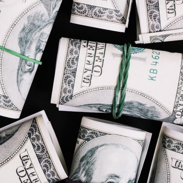 Uma visão aérea de enrolado nos nota de moeda de dólar em fundo preto Foto gratuita