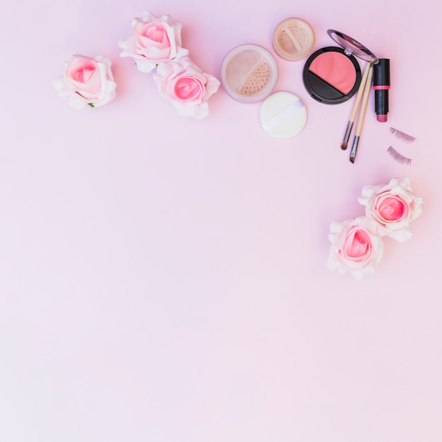Uma visão aérea de flores falsificadas com produtos cosméticos em pano de fundo rosa Foto gratuita