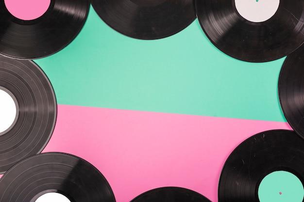 Uma visão aérea de fronteira de discos de vinil em fundo verde e rosa dual Foto gratuita
