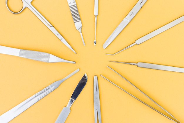 Uma visão aérea de instrumentos para cirurgia plástica em fundo amarelo Foto gratuita