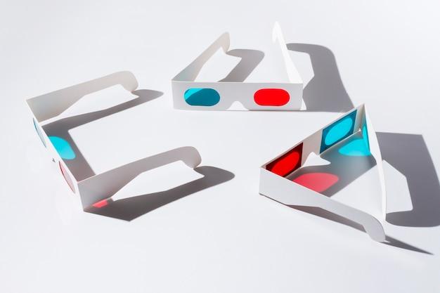 Uma visão aérea de óculos 3d vermelhos e azuis com sombra no pano de fundo branco Foto gratuita