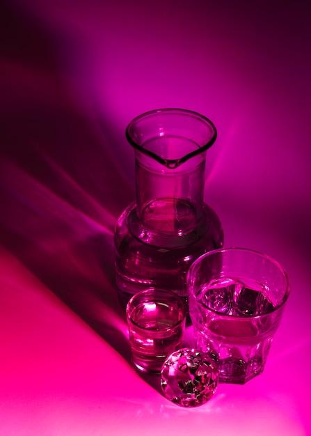 Uma visão aérea de óculos transparentes; copo e diamante no fundo rosa escuro Foto gratuita