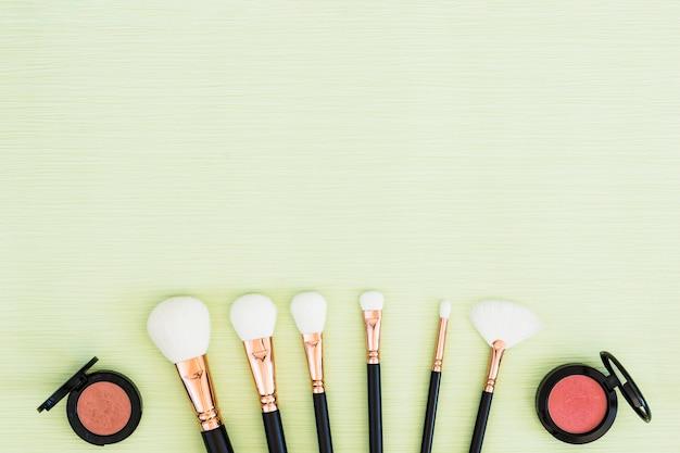 Uma visão aérea de pincéis de maquiagem branca e pó compacto rosa sobre fundo verde hortelã Foto gratuita