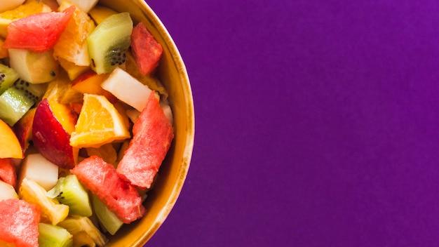Uma visão aérea de salada de frutas na tigela contra fundo roxo Foto gratuita