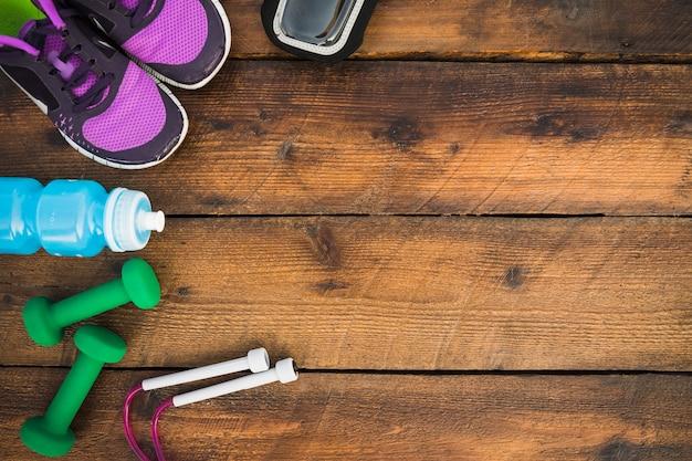 Uma visão aérea de sapatos; halteres; pular corda; garrafas de água na mesa de madeira Foto gratuita