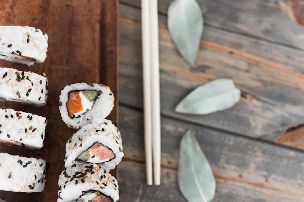 Uma visão aérea de sushi com pauzinhos sobre a mesa Foto gratuita