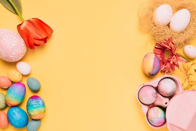 Uma visão aérea de tulipas frescas; gerbera e ovos de páscoa coloridos na superfície amarela Foto gratuita