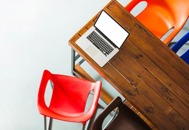 Uma visão aérea de um laptop aberto na mesa de madeira com cadeiras coloridas Foto gratuita