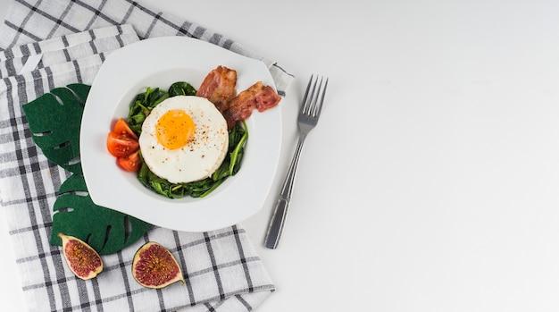 Uma visão aérea de um ovo frito com espinafre; tomate e bacon na chapa branca com guardanapo; garfo e figo fatia em fundo branco Foto gratuita
